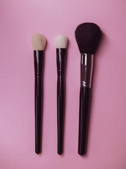 Trzy pędzle do makijażu na różowym tle. profesjonalne pędzelki do tuszu do rzęs i pudru. makijaż