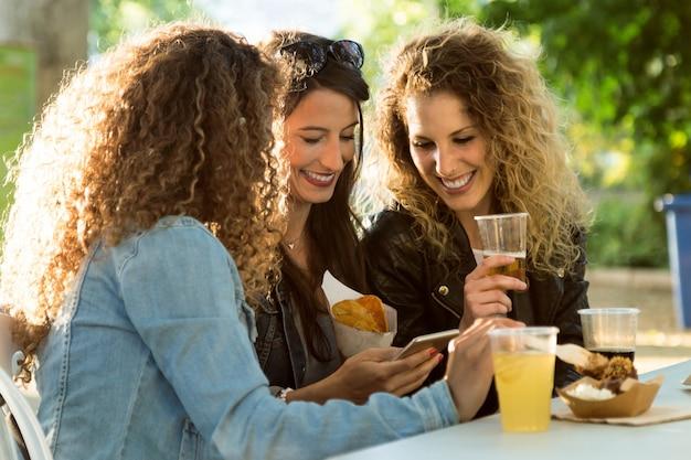 Trzy pi? kne m? ode kobiety przy u? yciu telefonu komórkowego na ulicy.