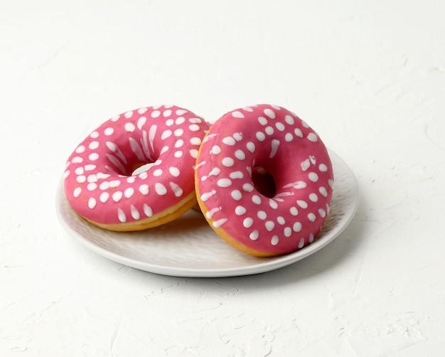 Trzy pieczone okrągłe pączki w białym okrągłym talerzu ceramicznym, z bliska