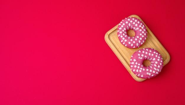 Trzy pieczone okrągłe pączki w różowej glazurze na czerwonym tle, kopia przestrzeń