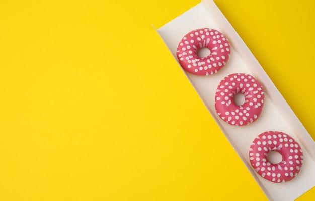 Trzy pieczone okrągłe pączki w różowej glazurze w białym kartonie na żółtym tle, widok z góry, miejsce na kopię