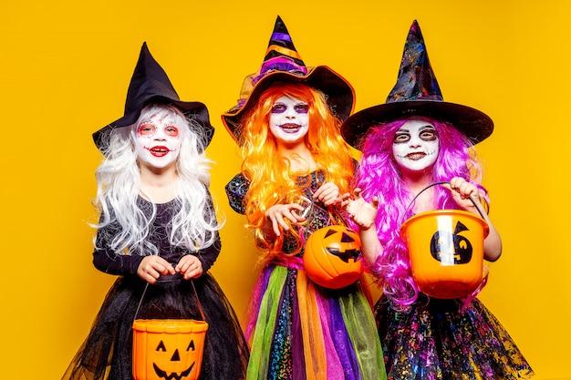 Trzy piękna dziewczyna w stroju czarownicy straszy i robi miny