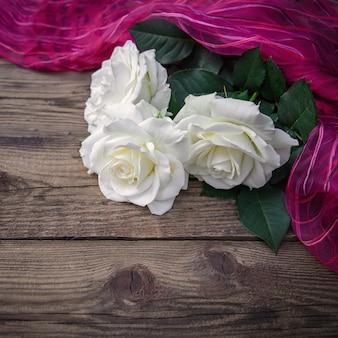 Trzy piękne białe róże i różowy materiał na drewnianej powierzchni