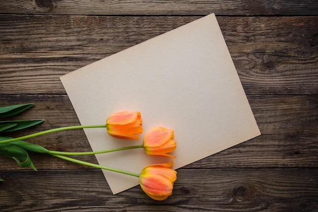 Trzy piękne delikatne pomarańczowe tulipany i kartka papieru do pisania po drewnianej powierzchni