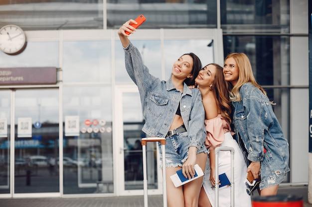 Trzy piękne dziewczyny stojące przy lotnisku