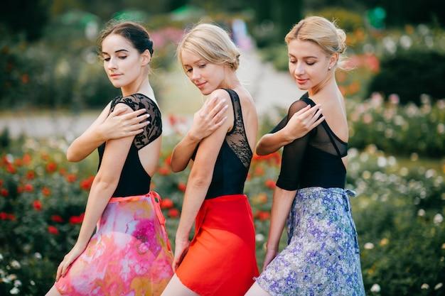 Trzy piękne dziewczyny w kolorowe sukienki pozowanie odkryty