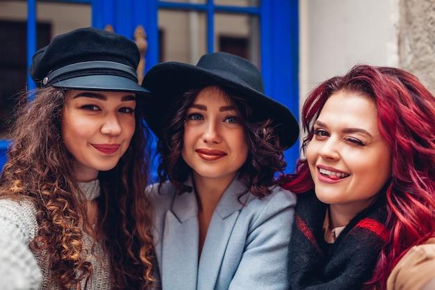 Trzy piękne kobiety przy selfie na ulicy miasta. szczęśliwi przyjaciele wiszą i bawią się na świeżym powietrzu. stylowe damskie
