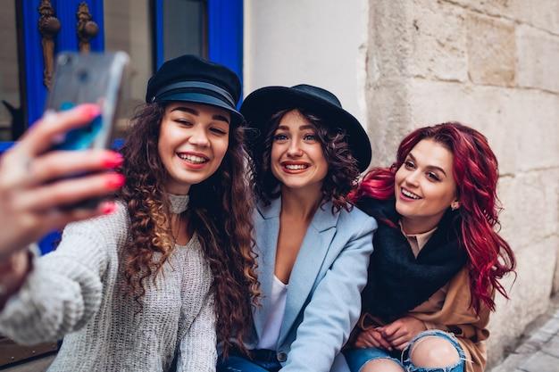 Trzy piękne kobiety przy selfie na ulicy miasta. szczęśliwi przyjaciele wiszą i bawią się na świeżym powietrzu
