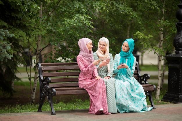 Trzy piękne młode kobiety w muzułmańskich sukienkach latem w parku z telefonami