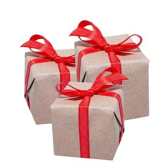 Trzy piękne owinięte pudełka z czerwoną wstążką na białym tle