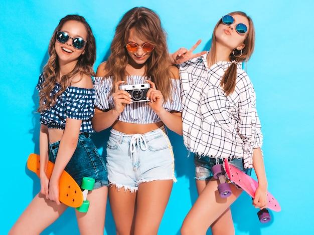 Trzy piękne stylowe uśmiechnięte dziewczyny z deskorolkami grosza w okularach przeciwsłonecznych. kobiety w letniej kraciastej koszuli. robienie zdjęć aparatem retro