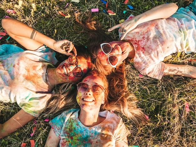 Trzy piękne uśmiechnięte dziewczyny pozują na imprezie holi