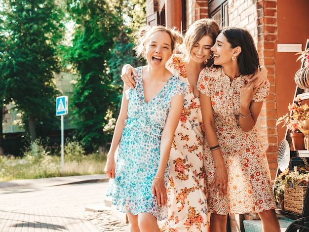 Trzy piękne uśmiechnięte dziewczyny w modnej letniej sukience pozowanie na ulicy