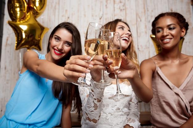 Trzy pięknej dziewczyny odpoczywa przy przyjęciem.