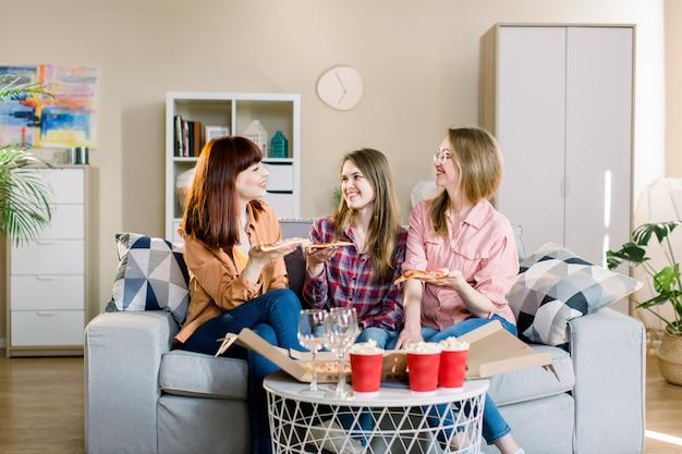 Trzy pięknej młodej kobiety je pizzę w domu. jedzenie fast food. szczęśliwi, piękni przyjaciele, śmiejąc się, jedząc pizzę na imprezie domowej. kobieta razem obiad, ciesząc się posiłkiem. czas wolny, przyjaźń