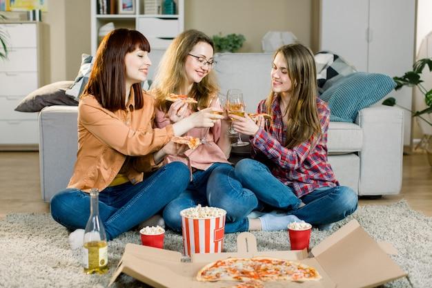 Trzy pięknej młodej kobiety pije wino i je pizzę w domu. szczęśliwi, piękni przyjaciele, śmiejąc się, jedząc pizzę na imprezie domowej. kobieta razem obiad, ciesząc się posiłkiem. czas wolny, przyjaźń