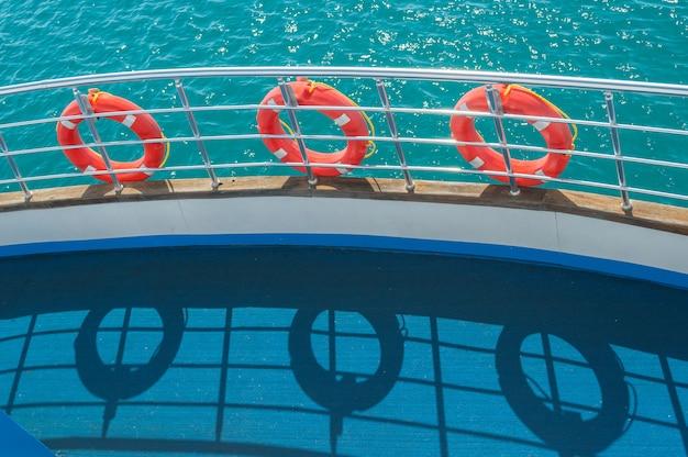 Trzy pierścienie kół ratunkowych na relingu statku i jego cienie