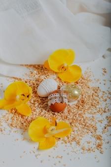 Trzy pisanki na białym tle z trocinami wokół. wesołych świąt kartka z żółtymi kwiatami orchidei. ozdoba wielkanocna z koronkową obwódką i sznurkiem. złote jajko wielkanocne.