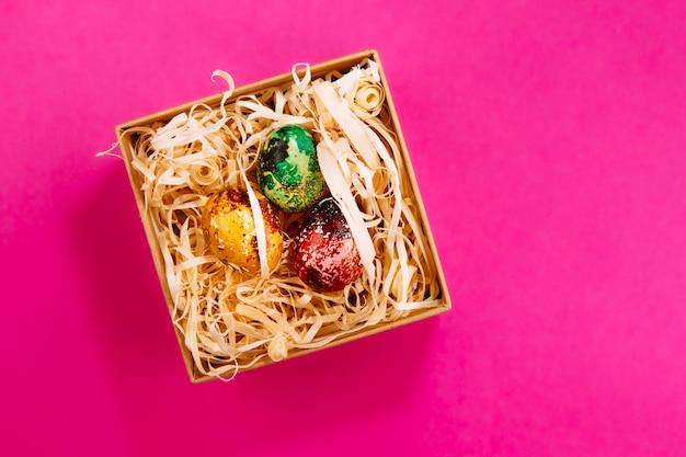 Trzy pisanki pomalowane na czerwono, zielono i żółto leżą w pudełku, w którym znajdują się drewniane wióry. malowane pisanki na różowym tle. skopiuj miejsce leżał płasko.