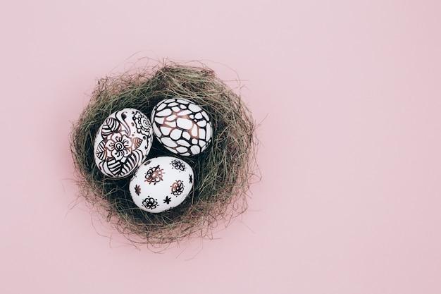 Trzy pisanki są pomalowane na czarno-biało, abstrakcja, leżą w zielonym gnieździe. malowane pisanki na różowym tle. leżał płasko. skopiuj miejsce