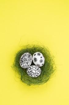 Trzy pisanki są pomalowane na czarno-biało, abstrakcja, leżą w zielonym gnieździe. malowane pisanki na żółtym tle. leżał płasko. skopiuj miejsce