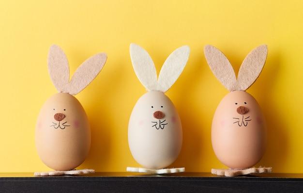 Trzy pisanki w kształcie króliczka na żółtym tle