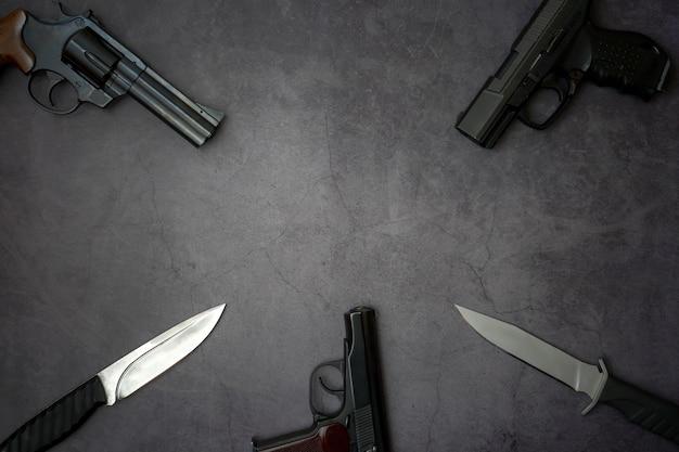 Trzy pistolety pistolety, noże wojskowe z bliska na szarym tle betonu.