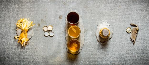 Trzy piwa, słony ser, zakrętki, sól i otwieracz do butelek na stole