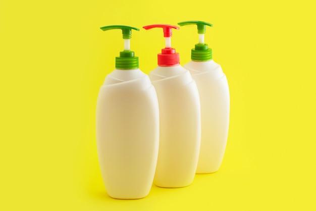 Trzy plastikowe butelki z dozownikiem na żółtym tle.