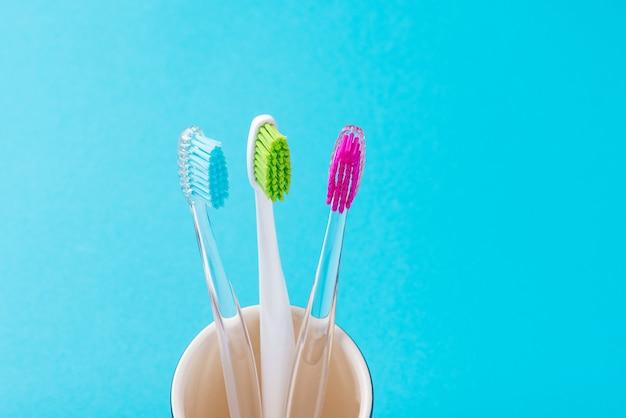 Trzy plastikowe kolorowe szczoteczki do zębów w szkle na niebieskim tle, z bliska