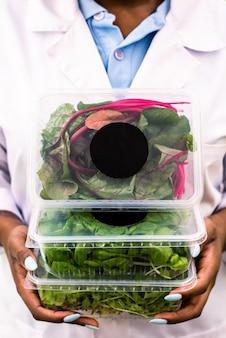 Trzy plastikowe pojemniki ze świeżymi liśćmi buraków i inną żywnością organiczną trzymane przez afrykańskiego pracownika szklarni