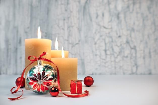 Trzy płonące świece ze złotymi dekoracjami świątecznymi