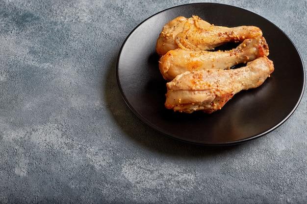 Trzy podudzia z kurczaka pieczone na czarnym talerzu