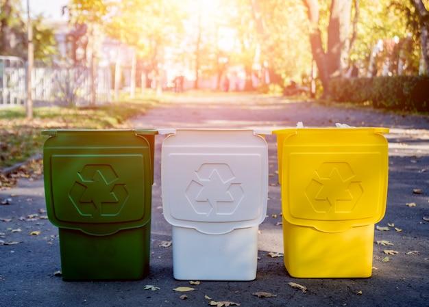 Trzy pojemniki na śmieci w innym kolorze, na sortowane odpady.