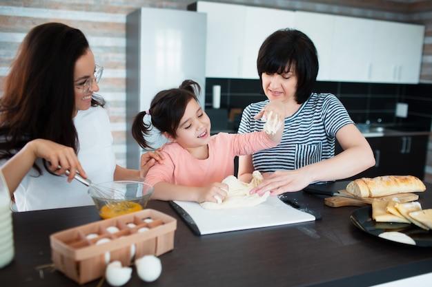 Trzy pokolenia kobiet gotują w kuchni. babciu, matka uczy wnuczkę gotowania. zagniatają ciasto razem.