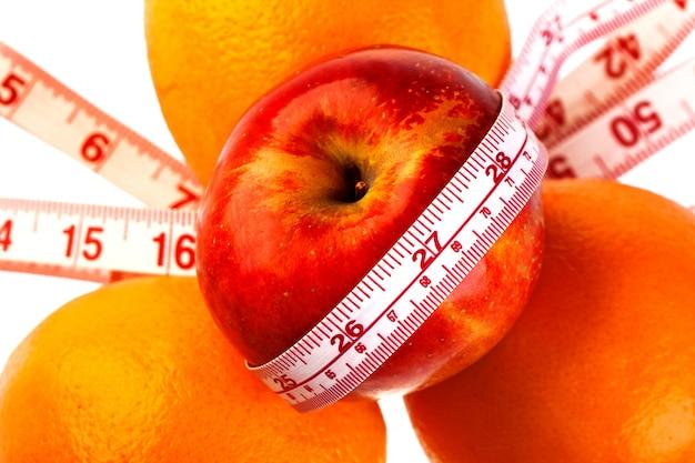Trzy pomarańcze i jabłko z linijką krawca. dieta witaminowa z owoców pomaga schudnąć.