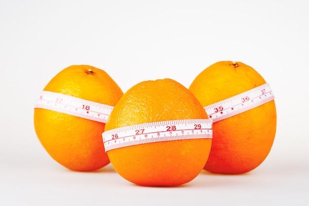 Trzy pomarańcze z linijką krawca. pomarańczowa dieta. owocowa dieta witaminowa pomaga schudnąć.