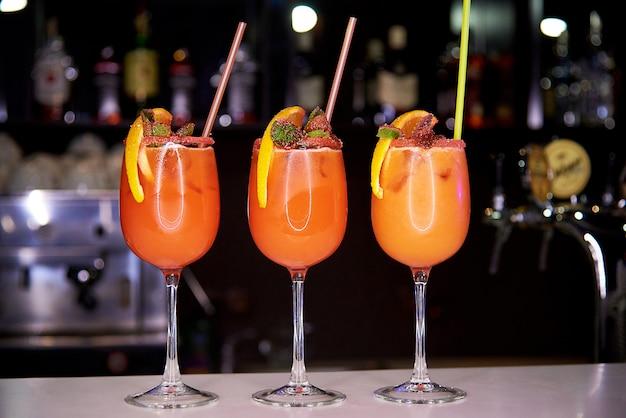 Trzy pomarańczowe zimne koktajle ozdobione okruchami cukru