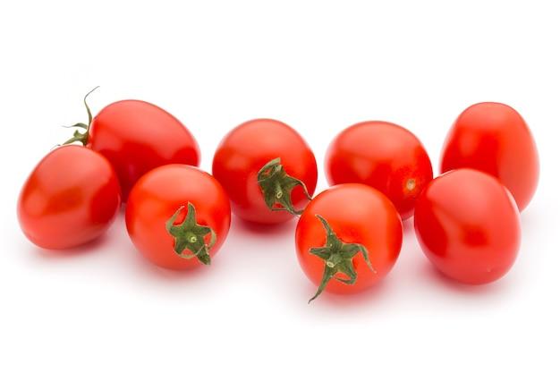 Trzy pomidory czereśniowe na białym.