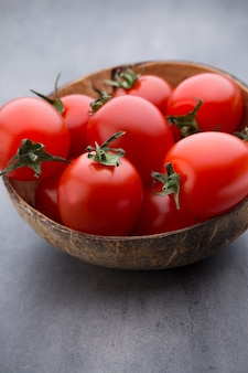Trzy pomidory czereśniowe w drewnianej misce na szaro.