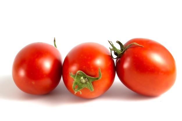 Trzy pomidory na białym tle.