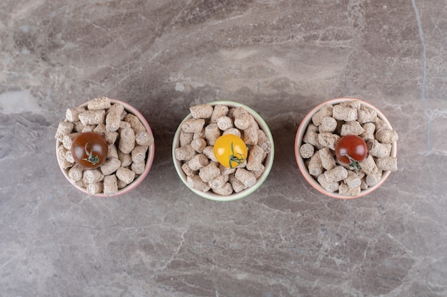 Trzy pomidory na bułce tartej w misce obok kolca, na marmurowej powierzchni