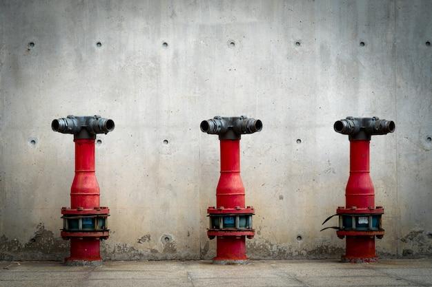 Trzy pompy bezpieczeństwa pożarowego na posadzce cementowej budynku betonowego. potopiony system przeciwpożarowy. ochrona przeciwpożarowa instalacji wodociągowej. czerwona pompa przeciwpożarowa przed betonową ścianą. wysokociśnieniowa pompa przeciwpożarowa.