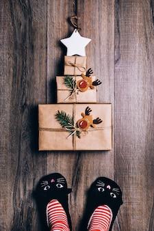 Trzy prezenty owinięte w brązowy papier ułożone w kształcie choinki z gwiazdą na górze. kobiece stopy w kotach kapcie, skarpetki w paski.