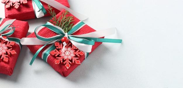 Trzy prezenty w czerwonym papierze z płatki śniegu i wstążkami na jasnej powierzchni. prezenty świąteczne.