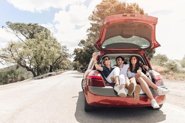 Trzy przyjaciela siedzi wpólnie w samochodowym bagażniku bierze autoportret na drodze