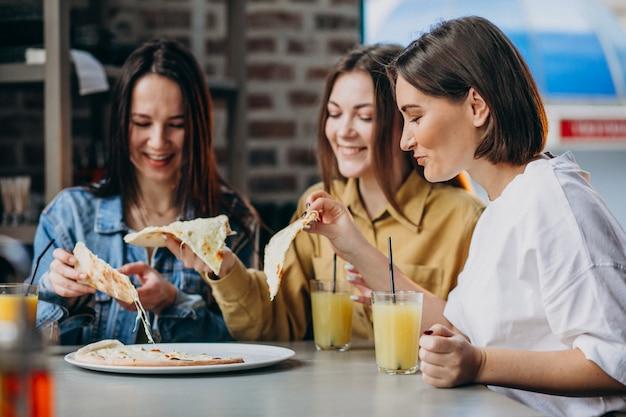 Trzy przyjaciółki o pizzę w barze