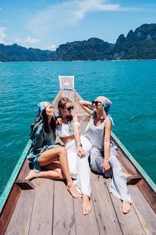 Trzy przyjaciółki turystki podróżują po parku narodowym khao sok na wakacjach w tajlandii. żeglowanie na azjatyckiej łodzi po jeziorze w słoneczny dzień, z niesamowitym widokiem.