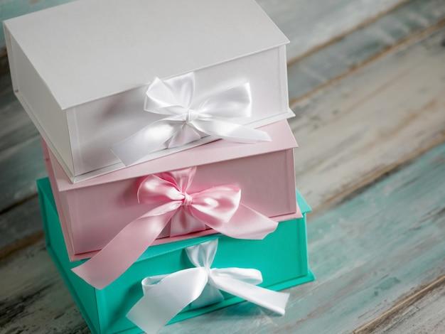 Trzy pudełka na prezenty, biały, różowy i turkusowy. widok z góry po przekątnej na drewnianym stole