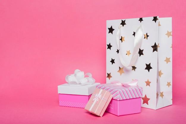Trzy pudełka na prezenty i zakupy torby papierowe na różowym tle